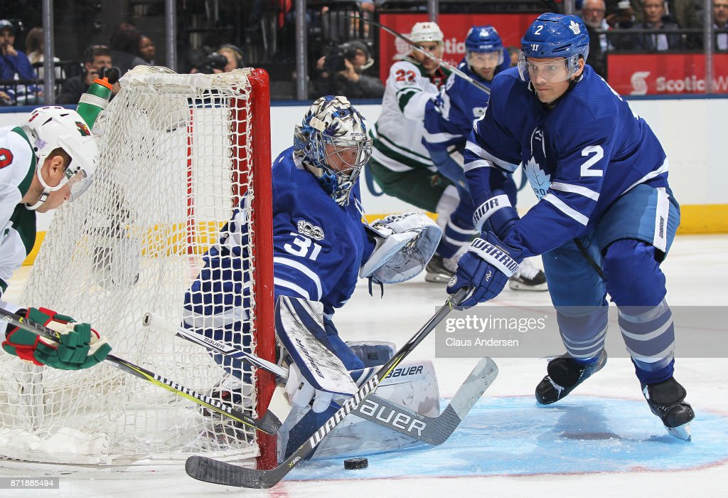 Frederik Andersen #31 and Ron Hainsey #2 of the Toronto Maple Leafs cover the corner against Mikko Koivu #9 of the Minnesota Wild during an NHL game at the Air Canada Centre on November 8, 2017 in Toronto, Ontario, Canada. The Maple Leafs defeated the Wild 4-2.