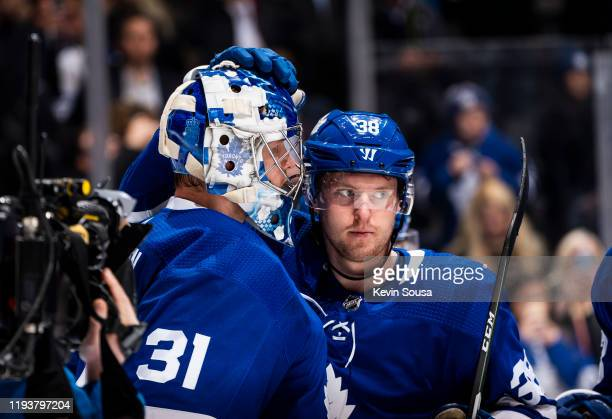 Frederik Andersen of the Toronto Maple Leafs celebrates with teammate Rasmus Sandin after defeating the New Jersey Devils at the Scotiabank Arena on...
