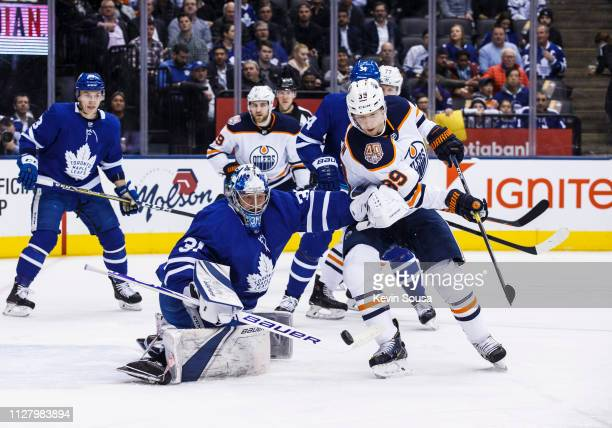 Frederik Andersen of the Toronto Maple Leafs deflects a loose puck as Alex Chiasson of the Edmonton Oilers battles during the first period at the...