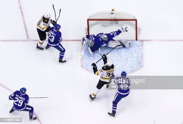 Frederik Andersen of the Toronto Maple Leafs makes a glove save as Patrick Marleau battles in front against Patrice Bergeron of the Boston Bruins...