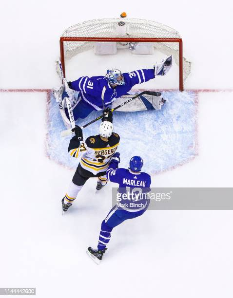 Frederik Andersen of the Toronto Maple Leafs makes a glove save in front of teammate Patrick Marleau as Patrice Bergeron of the Boston Bruins crashes...