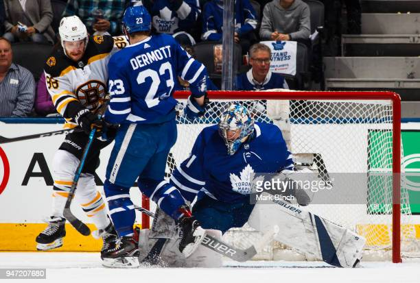 Frederik Andersen of the Toronto Maple Leafs makes a save as teammate Travis Dermott clears David Pastrnak of the Boston Bruins from the crease in...