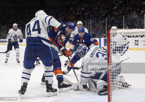 Frederik Andersen of the Toronto Maple Leafs makes the stop on Matt Martin and Cal Clutterbuck of the New York Islanders during the second period at...