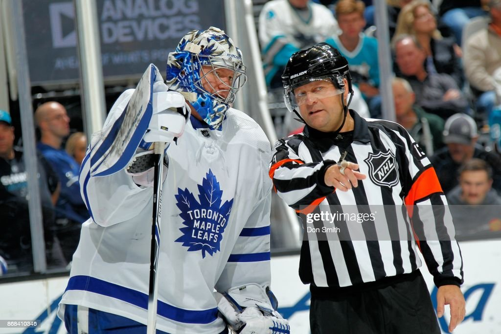 Frederik Andersen #31 of the Toronto Maple Leafs talks with Referee Dan O'Halloran #13 at SAP Center on October 30, 2017 in San Jose, California.