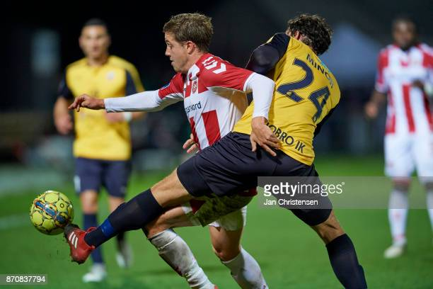 Frederik Borsting of AaB Aalborg and Rasmus Minor Petersen of Hobro IK compete for the ball during the Danish Alka Superliga match between Hobro IK...