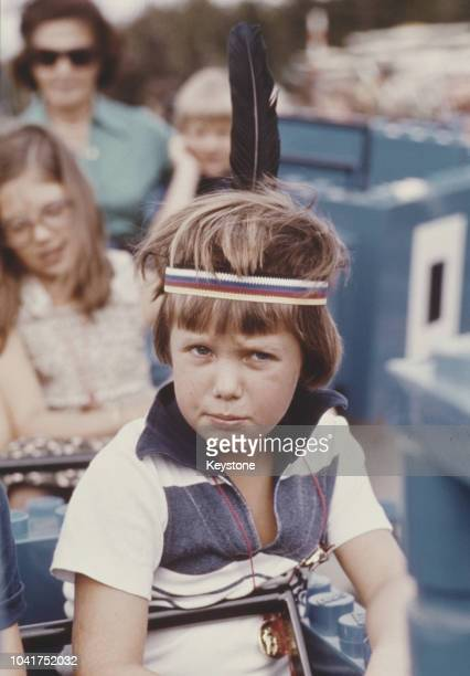 Frederik Crown Prince of Denmark wearing a feather headdress at a fun centre 1977