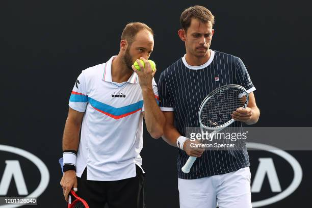 Frederik Nielsen of Denmark and Tim Puetz of Germany talk tactics in their Men's Doubles first round match against John Peers of Australia and...