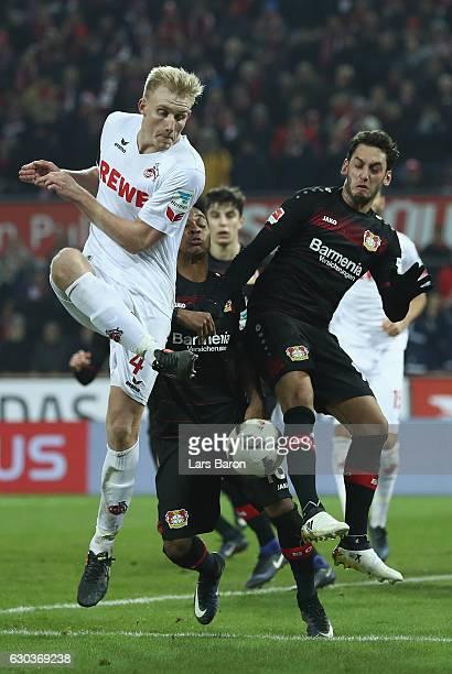 Frederik Soerensen of Koeln is challenged by Wendell of Bayer Leverkusen and Hakan Calhanoglu of Bayer Leverkusen during the Bundesliga match between...