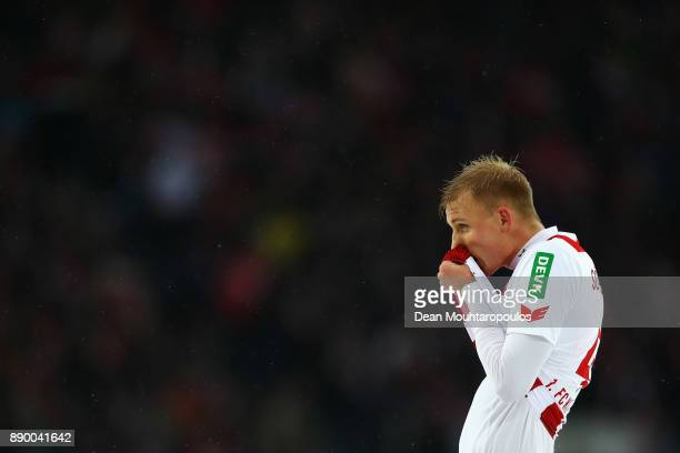 Frederik Sorensen of FC Koeln wipes is nose as snow falls during the Bundesliga match between 1 FC Koeln and SportClub Freiburg at...