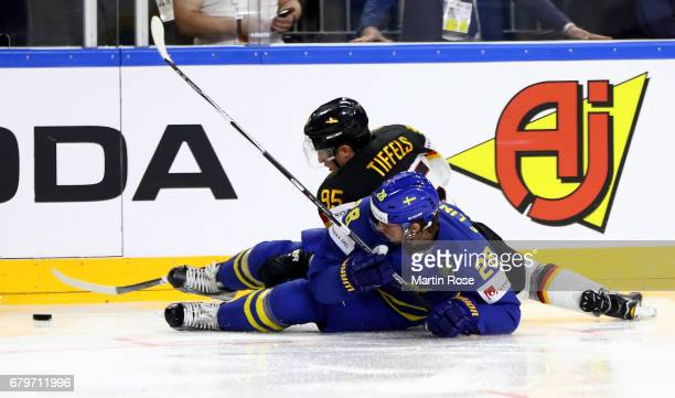 Frederik Tiffels of Germany challenges Elias Lindholm of Sweden for the puck during the 2017 IIHF Ice Hockey World Championship game between Germany...