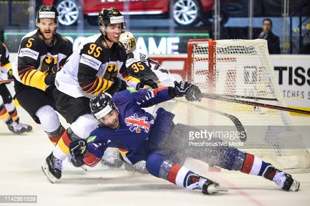 Frederik Tiffels of Germany checks Matthew Myers of Great Britain during the 2019 IIHF Ice Hockey World Championship Slovakia group A game between...