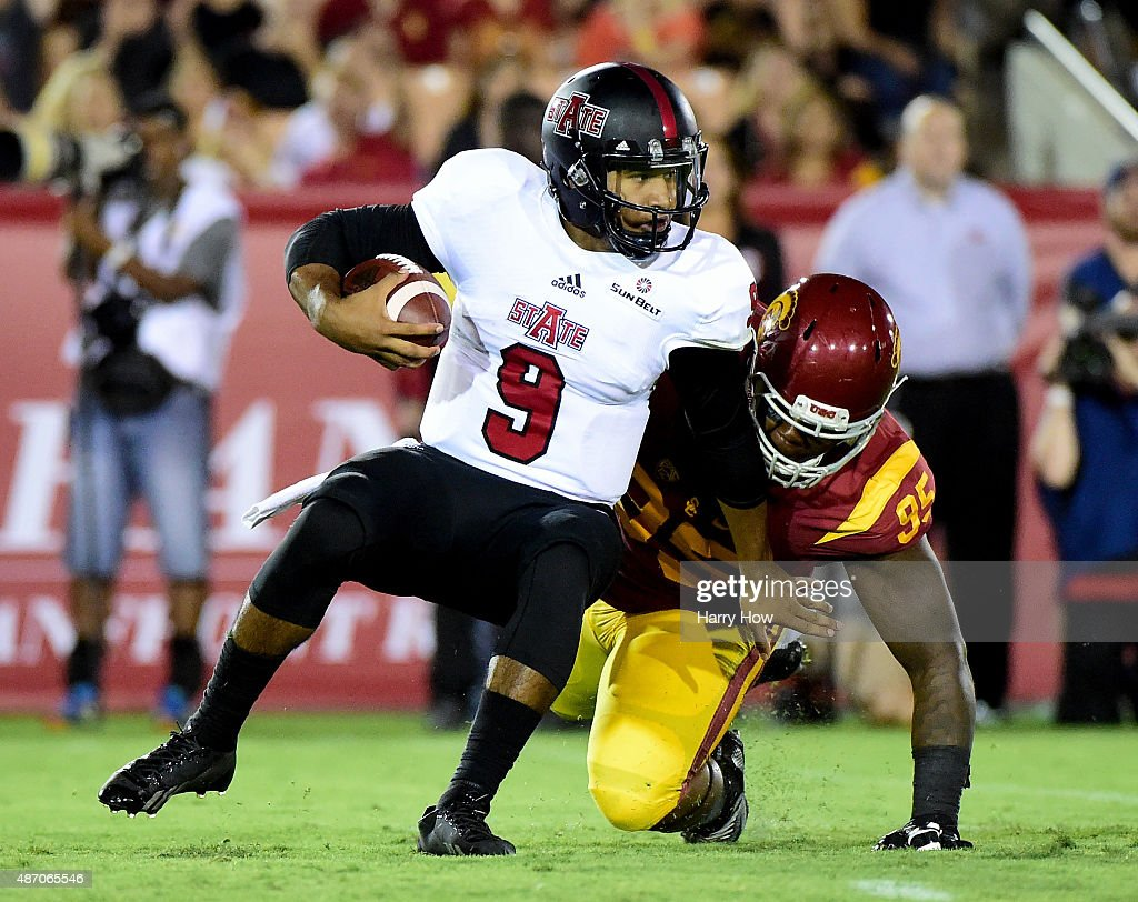 Fredi Knighten #9 of the Arkansas State Red Wolves is sacked by Kenny Bigelow #95 of the USC Trojans during the first quarter at Los Angeles Coliseum on September 5, 2015 in Los Angeles, California.