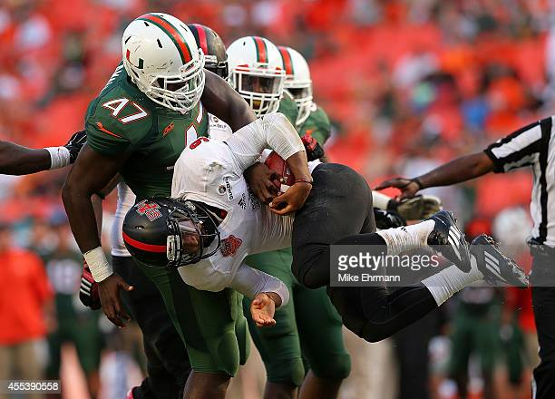 Fredi Knighten of the Arkansas State Red Wolves is sacked by Ufomba Kamalu of the Miami Hurricanes during a game at Sunlife Stadium on September 13...