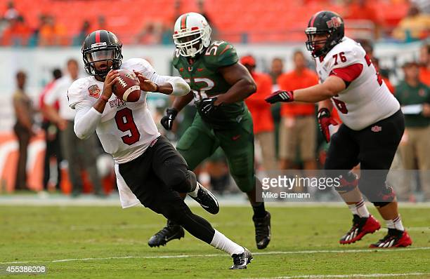 Fredi Knighten of the Arkansas State Red Wolves looks to pass during a game against the Miami Hurricanes at Sunlife Stadium on September 13 2014 in...