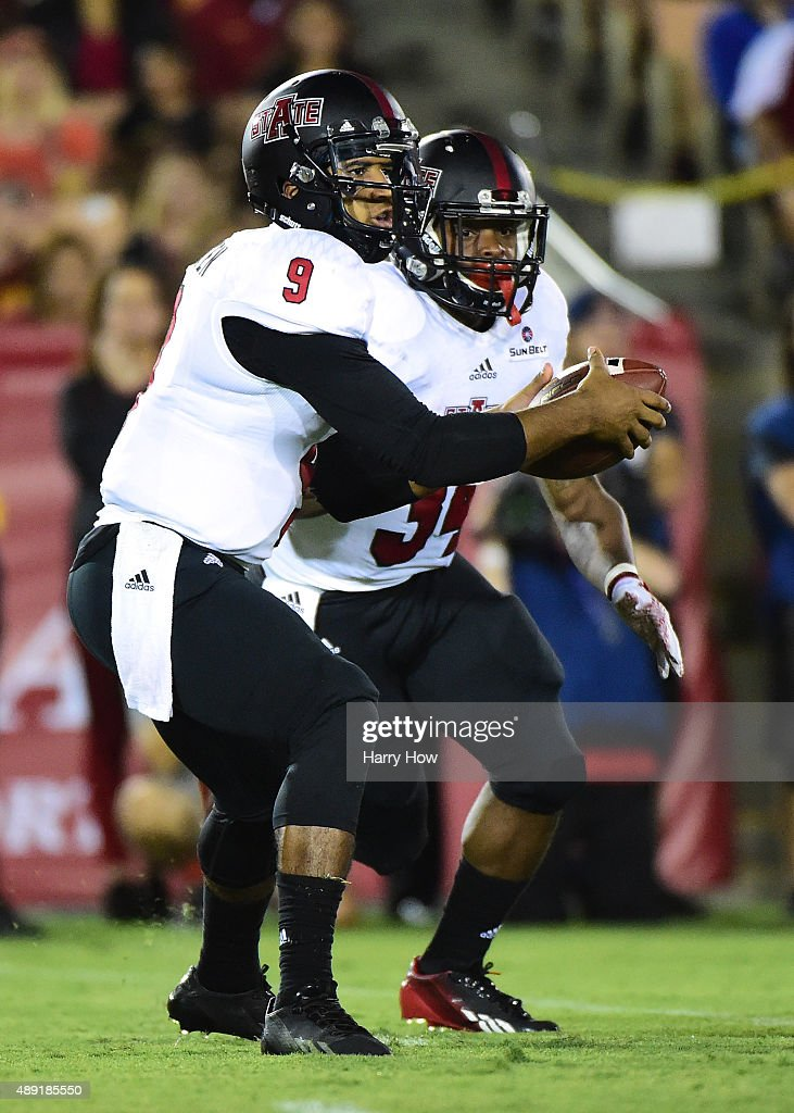 Fredi Knighten #9 of the Arkansas State Red Wolves takes a snap in front of Michael Gordon #34 during the game against the USC Trojans at Los Angeles Coliseum on September 5, 2015 in Los Angeles, California.