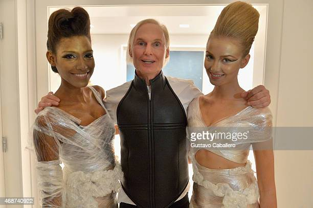 Fredric S Brandt poses with models at the viewing of his Art Collection cocktail party on December 4 2012 in Coconut Grove Florida