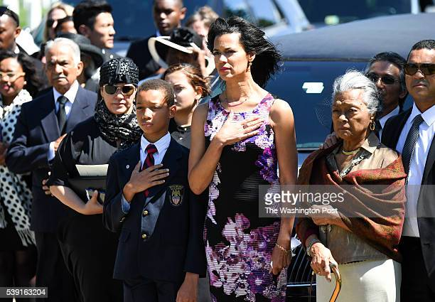 Fredricka Whitfield and her son John Glenn Jr along with his widow Nola Whitfield place their hands over their hearts during the military funeral...