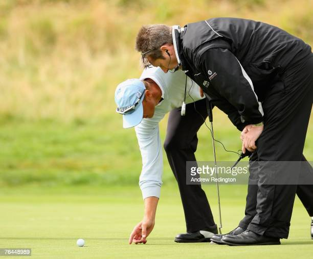 Fredrik Andersson Hed of Sweden talks to a rules official after his ball moved due to high winds on the 18th green during the third round of The...