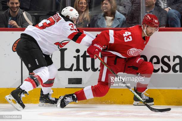 Fredrik Claesson of the New Jersey Devils battles along the boards for position with Darren Helm of the Detroit Red Wings during an NHL game at...