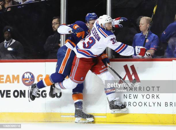 Fredrik Claesson of the New York Rangers checks Johnny Boychuk of the New York Islanders into the boards during the second period at the Barclays...