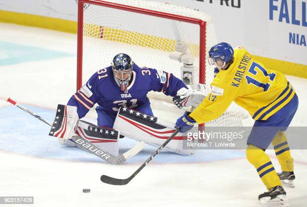 Fredrik Karlström of Sweden passes the puck in front of Joseph Woll of United States during the third period of play in the IIHF World Junior...
