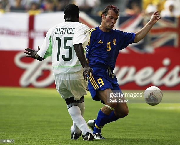 Fredrik Ljungberg of Sweden tackles Justice Christopher of Nigeria during the FIFA World Cup Finals 2002 Group F match played at the Kobe Wing...