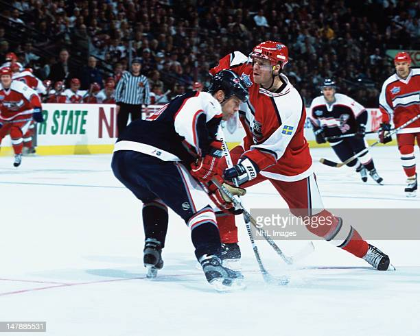 Fredrik Modin of Team World and the Tampa Bay Lightning shoots the puck past Scott Stevens of Team North America and the New Jersey Devils during the...