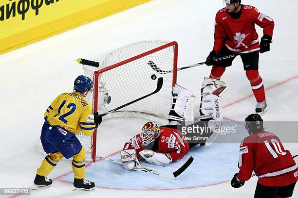 Fredrik Pettersson of Sweden scores his team's fourth goal against goalkeeper Tobias Stephan, Timo Helbling and Andreas Ambuhl of Switzerland during...