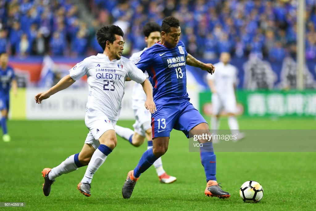 Fredy Guarin #13 of Shanghai Shenhua and Lee Ki-Je #23 of Suwon Samsung Bluewings compete for the ball during the 2018 AFC Champions League Group H match between Shanghai Shenhua and Suwon Samsung Bluewings at Hongkou Football Stadium on March 13, 2018 in Shanghai, China.