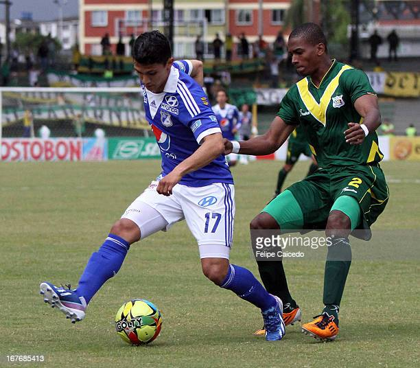 Fredy Montero of Millonarios struggles for the ball with Edwar Zea of Deportes Quindio during a match between Millonarios and Deportes Quindio as...