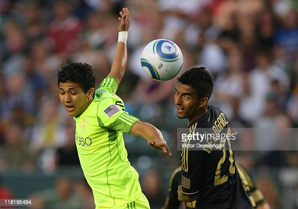 Fredy Montero of the Seattle Sounders and AJ DeLaGarza 20 of the Los Angeles Galaxy vie for the high ball in the first half during their MLS match at...