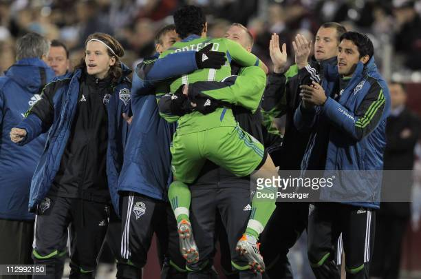 Fredy Montero of the Seattle Sounders FC jumps into the arms of his teammates as he celebrates his goal against the Colorado Rapids in the 19th...