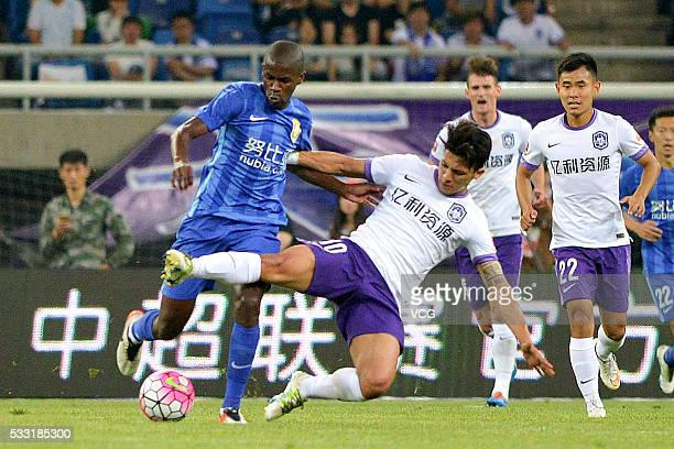 Fredy Montero of Tianjin Teda and Ramires of Jiangsu Suning compete for the ball during Chinese Football Association Super League Round 10 between...