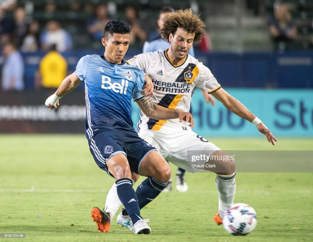 Fredy Montero #12 of Vancouver Whitecaps battles Joao Pedro #8 of Los Angeles Galaxy during the Los Angeles Galaxy's MLS match against Vancouver Whitecaps at the StubHub Center on July 19, 2017 in Carson, California. Vancouver won the match 1-0