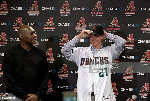 Free agent aquisition Zack Greinke of the Arizona Diamondbacks tries on his new hat as General Manager Dave Stewart looks on during a press...