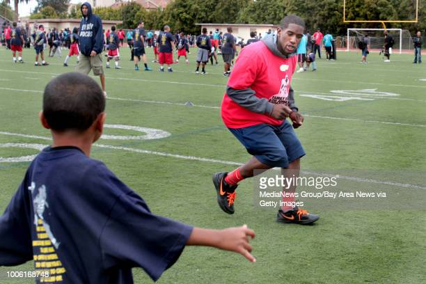 NFL free agent Jacksonville line backer Alvin Bowen gives instructions to kids on a drill during the 6th Annual Fam 1st Family Football Camp at the...