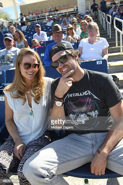 Free agent pitcher and former Oakland Athletics Barry Zito sits in the stands with his wife Amber prior to the spring training game between the...