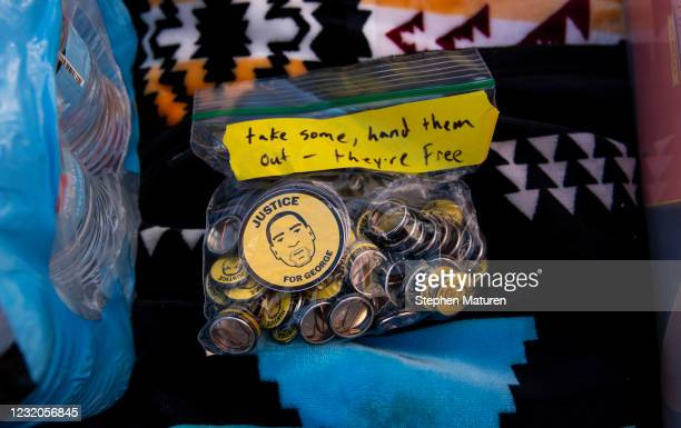 Free buttons with an image of George Floyd's face are made available outside the Hennepin County Government Center on April 1, 2021 in Minneapolis,...