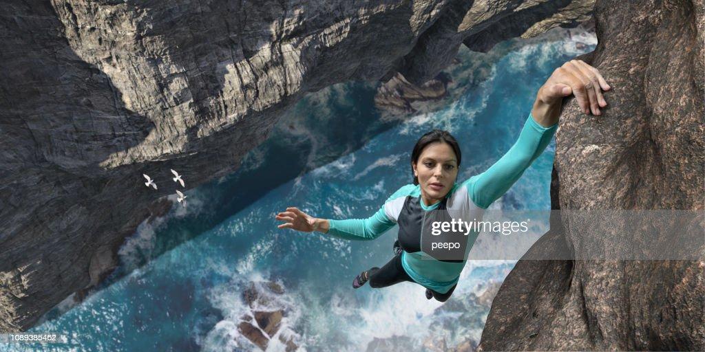 無料登山者は海崖の岩の表面に片手をハングアップします。 : ストックフォト