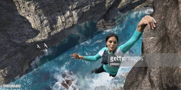free climber hangs one handed on sea cliff rock face - coraggio foto e immagini stock