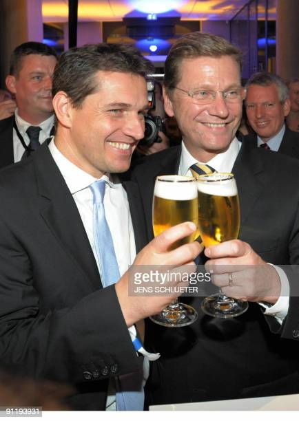 Free Democrats party leader Guido Westerwelle and his partner Michael Mronz pose with a beer during the FDP election evening after parliamentary...
