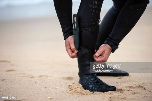Free diver aligning ankle wetsuit panels, strapping dive knife.