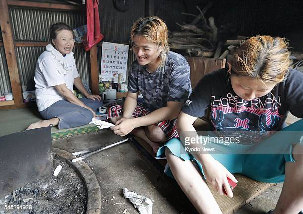 Free diver Yushi Ikeda chats with wife and fellow diver Mana and veteran diver Noriko Minami, with a 28-year career, in a hut for divers in the Azena...