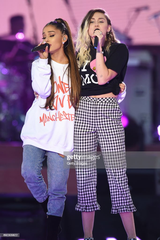 NO SALES, free for editorial use. In this handout provided by 'One Love Manchester' benefit concert (L) Ariana Grande and Miley Cyrus perform on stage on June 4, 2017 in Manchester, England. Donate at www.redcross.org.uk/love