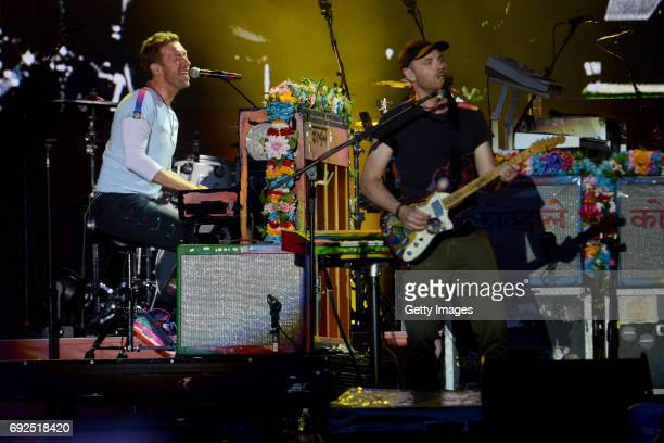 SALES free for editorial use In this handout provided by 'One Love Manchester' benefit concert Chris Martin and Jonny Buckland of Coldplay perform on...