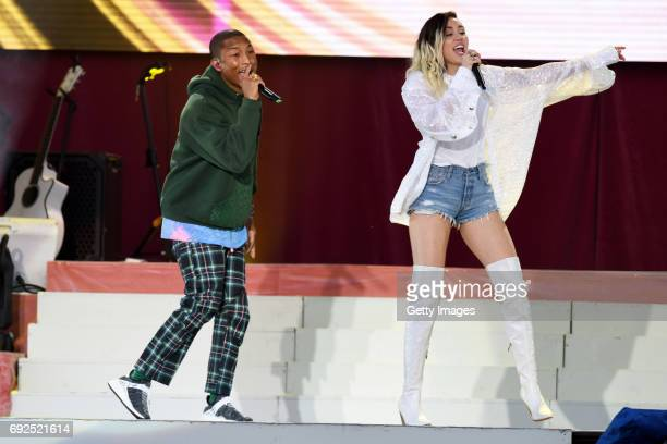 SALES free for editorial use In this handout provided by 'One Love Manchester' benefit concert Pharrell Williams and Miley Cyrus perform on stage on...