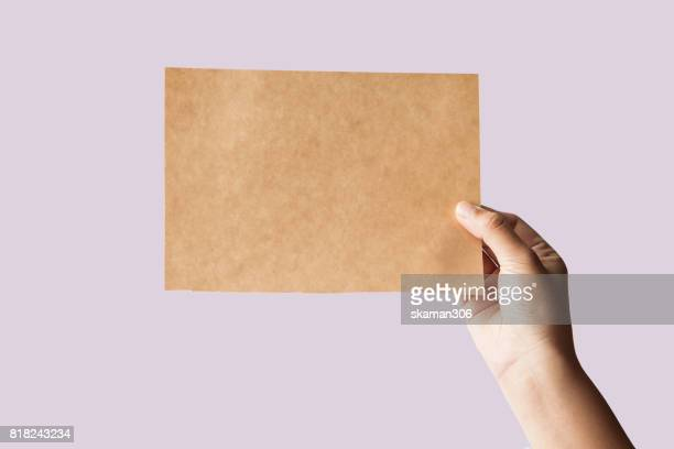 free hand holding blank paper with pastel background