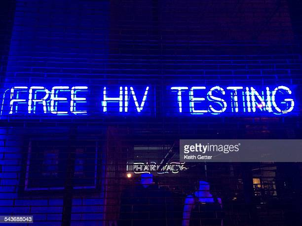 'Free HIV Testing' is spelled out in blue white neon letters hanging in a storefront window behind security gates in Boerum Hill Brooklyn NYC March 9...