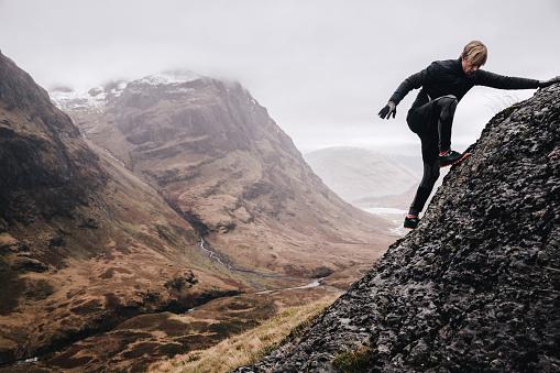 A free runner climbs a steep mountain rock face - gettyimageskorea
