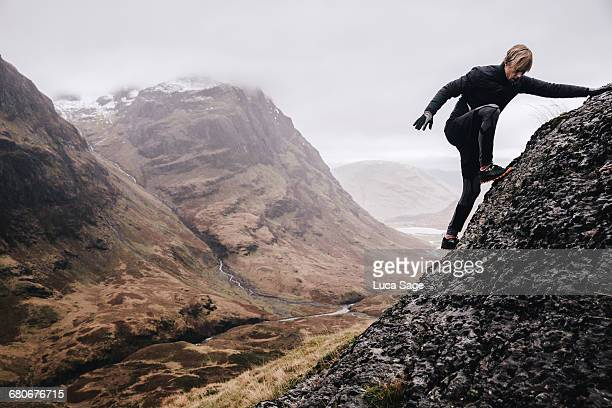 A free runner climbs a steep mountain rock face